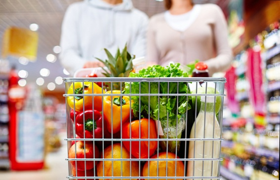 Image of cart full of products in supermarket being pushed by couple